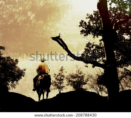 A cowboy rides his horse into the mountains. - stock photo