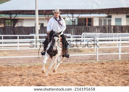 A cowboy riding a horse in his farm - stock photo