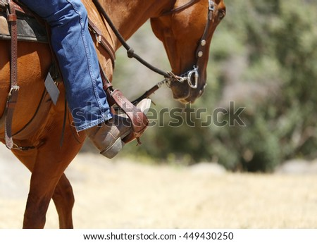 A cowboy riding a horse with an up close view of a boot and stirrup.  - stock photo