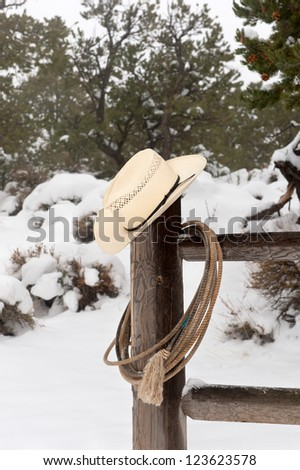 A cowboy's wrangler hat and lasso hanging on a corral fence post in a snowy, mountain ranch. - stock photo