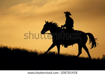 A cowboy silhouette riding on a mountain with an yellow sky. - stock photo