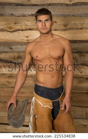A cowboy standing with his bare torso holding on to a hat.