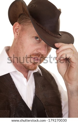 A cowboy up close with his hand on his hat. - stock photo
