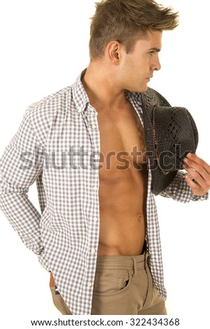 A cowboy with his shirt undone showing off his fit chest holding on to his western hat. - stock photo