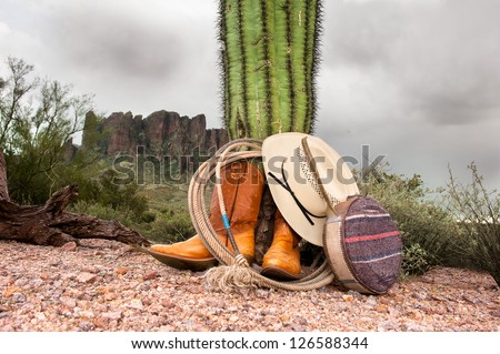 A cowboy wranglers boots, hat, lasso and canteen rest against a cactus in extreme, rugged desert terrain. - stock photo