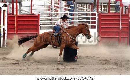 a cowgirl competing in a barrel race - stock photo