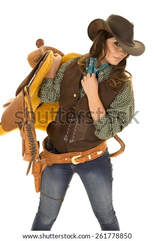 A cowgirl holding on to her saddle on her shoulder.