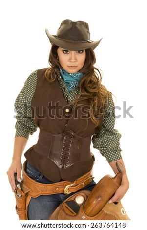 a cowgirl holding on to her saddle with her hand on her pistol ready to go.