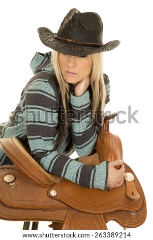a cowgirl in her poncho and black hat, leaning on her saddle.