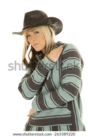 A cowgirl in her poncho and western hat, looking to the side. - stock photo