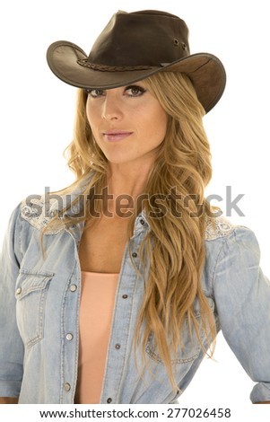 A cowgirl in her western hat with a playful expression.