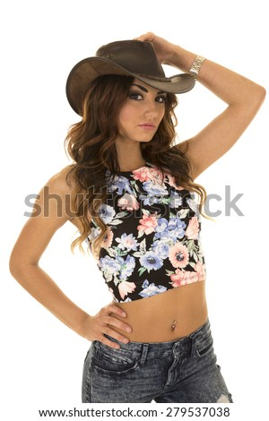 a cowgirl in her western hat with her floral crop top on. - stock photo