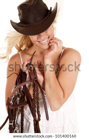 A cowgirl is standing with a hat on holding a bridle. - stock photo