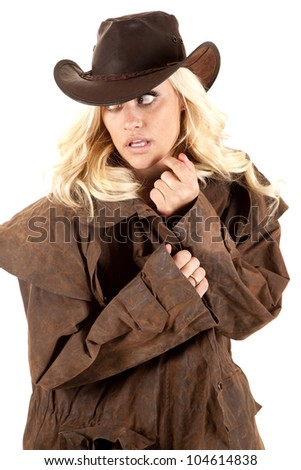 A cowgirl is wearing a duster and looking off to the side. - stock photo
