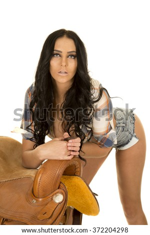 a cowgirl leaning over her saddle with a sensual expression. - stock photo
