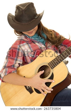 A cowgirl looking down playing her guitar. - stock photo