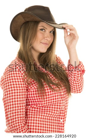 A cowgirl looking to the side, touching the brim of her hat. - stock photo