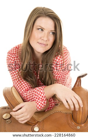 a cowgirl looking to the side, with her elbows on the saddle. - stock photo