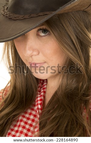 A cowgirl peeking out from under her western hat. - stock photo