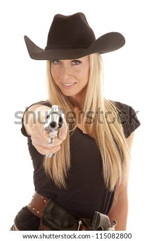 A cowgirl pointing her pistol at the camera with a smile  on her face. - stock photo