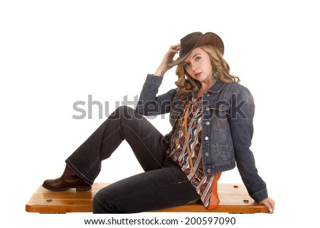 a cowgirl sitting on a bench in her western wear looking.
