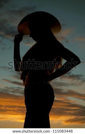 A cowgirl standing holding on to the brim of her hat with a beautiful sunset in the background. - stock photo