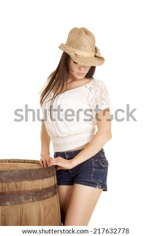 A cowgirl standing next to a barrel in her western hat and short shorts. - stock photo