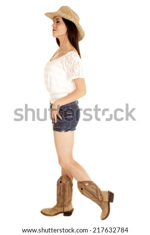 A cowgirl standing with her eyes closed in her short denim shorts and boots. - stock photo