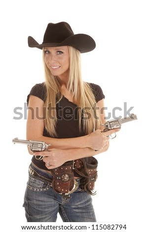 A cowgirl standing with her pistols in her hands and her holsters on her hips. - stock photo