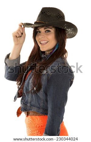 a cowgirl touching the brim of her hat with a smile on her face. - stock photo