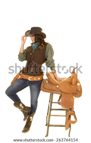 a cowgirl touching the brim of her hat with her foot up