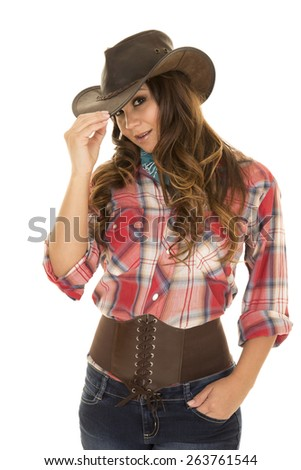 a cowgirl touching the brim of her hat with her hand in her pocket. - stock photo