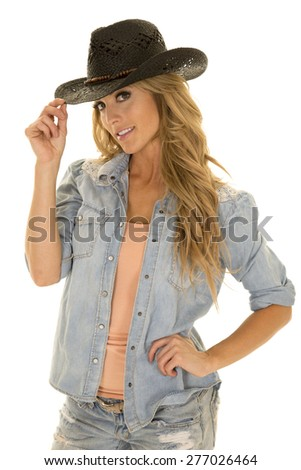 A cowgirl touching the brim of her western hat. - stock photo