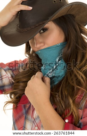 a cowgirl with a bandanna over her face, holding on to her hat. - stock photo