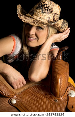 A cowgirl with a big smile leaning on her saddle. - stock photo