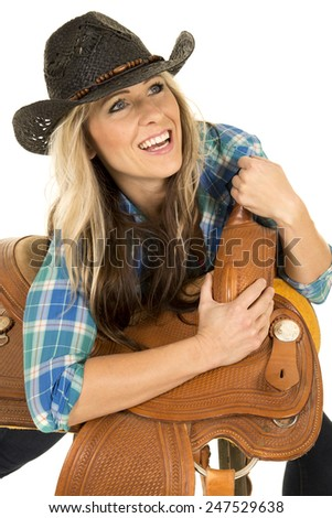 A cowgirl with a big smile on her face looking up and leaning on her saddle. - stock photo