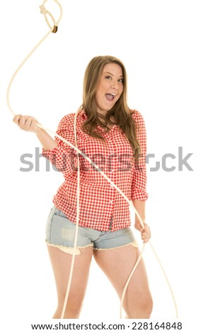 a cowgirl with a big smile spinning a rope - stock photo