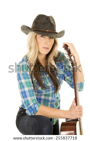 a cowgirl with a serious expression on her face holding on to her guitar. - stock photo