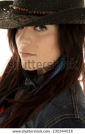 a cowgirl with a serious expression on her face looking out from under her hat. - stock photo