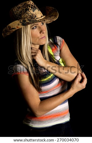 a cowgirl with a serious expression on her face, with her western hat on. - stock photo