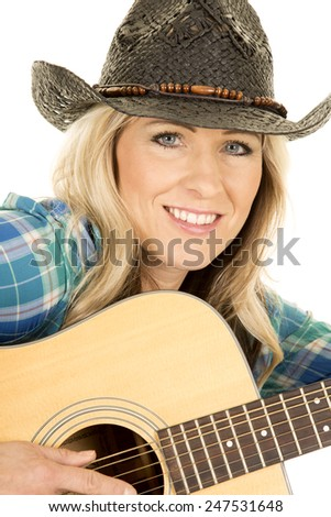 A cowgirl with a smile on her face, with her hand on her guitar. - stock photo
