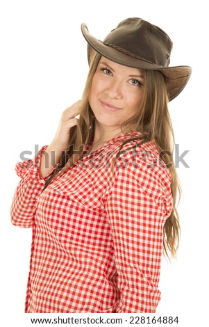 A cowgirl with her hand in her hair wearing her hat. - stock photo