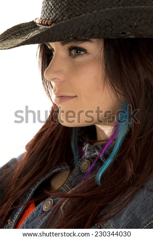 a cowgirl with her head to the side, with a small smile on her lips. - stock photo