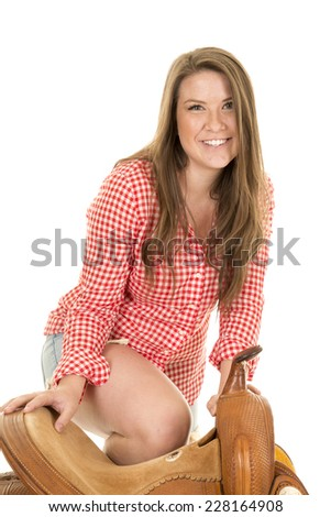 A cowgirl with her knee on the saddle with a smile - stock photo