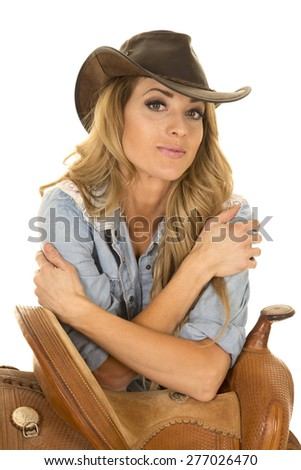 a cowgirl with her western hat on, leaning on her saddle. - stock photo