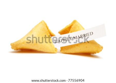 A cracked open fortune cookie saying happily married. - stock photo