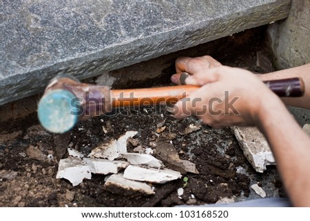 A craftsman holds a hammer and chisels and removed mortar - stock photo