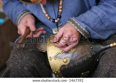 A craftsman making a medieval soldiers helmet the oldfashioned way, - stock photo