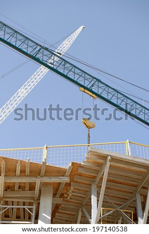 A crane assisting with the construction of a building. - stock photo