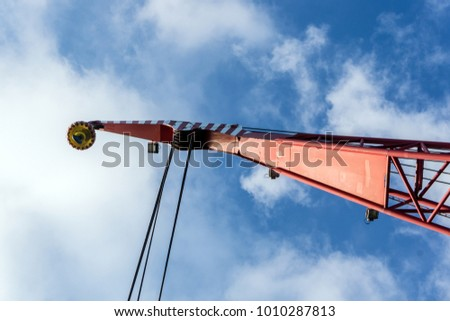 A crane boom on a construction barge lowering the main block at oil field